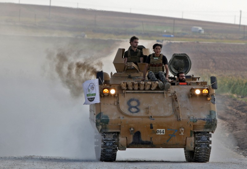 Turkish-backed Syrian fighters patrol the northern Syrian Kurdish town of Tal Abyad on the border with Turkey on Oct. 31.