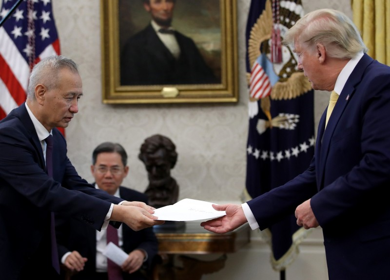 Chinese Vice Premier Liu He presents U.S. President Donald Trump with a letter from Chinese President Xi Jinping after the two discussed a U.S.-China trade agreement.