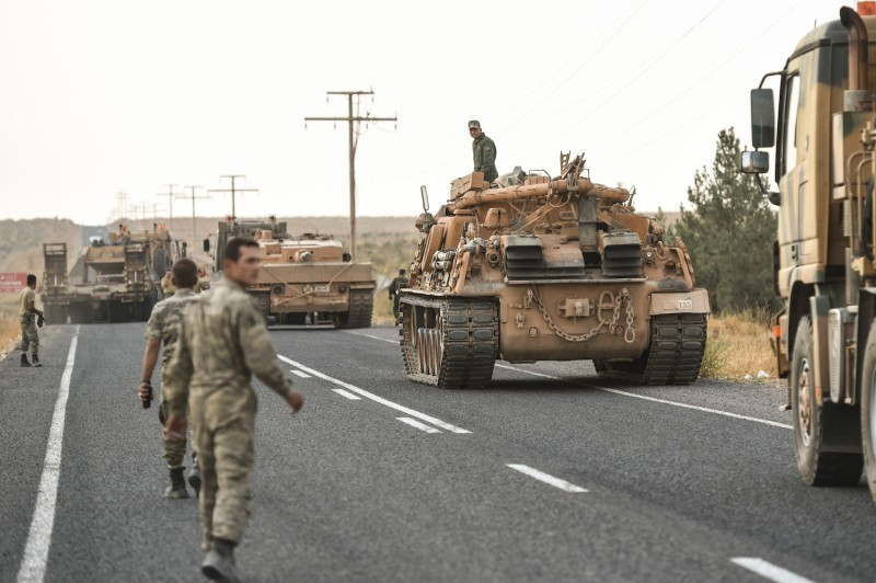 Turkish soldiers secure a road before army tanks start moving toward the Syrian border in Ceylanpinar, Turkey, on Oct. 18.