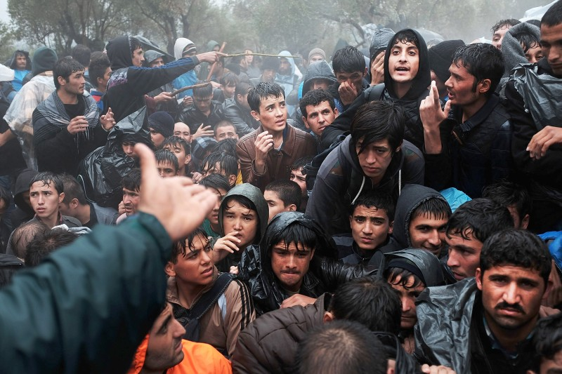 Afghan men gather outside the main gate of the Moria camp as migrants wait to be processed on the Greek island of Lesbos on Oct. 22, 2015.
