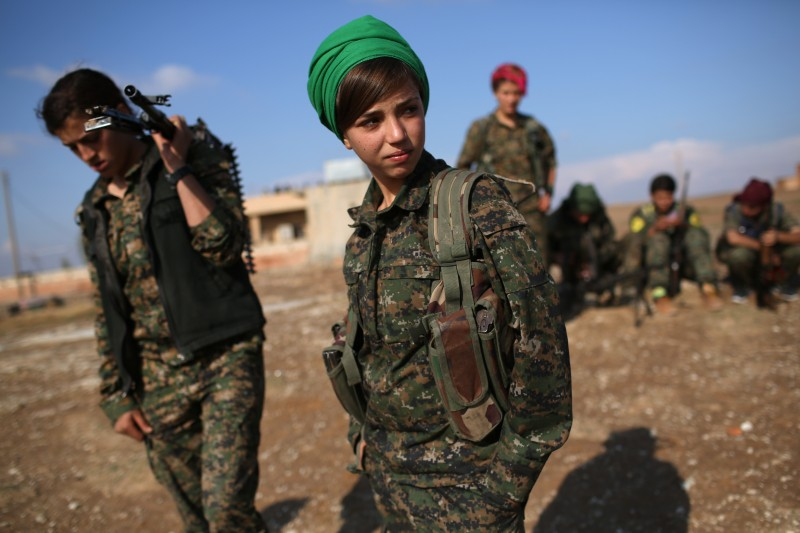 Kurdish female troops from the Syrian Democratic Forces overlook the front line.