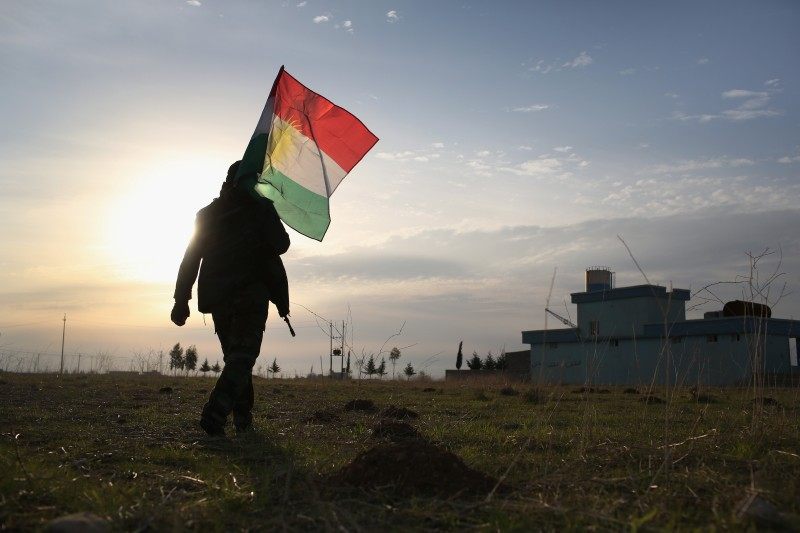 A Peshmerga soldier places a Kurdish flag near the front line with the Islamic State in Iraq.
