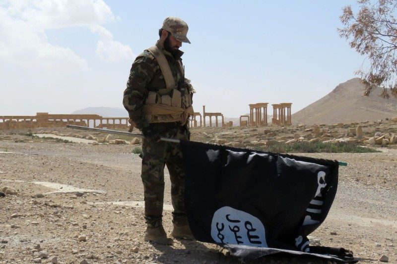 A member of the Syrian pro-government forces carries an Islamic State flag as he stands on a street in Palmyra on March 27, 2016.