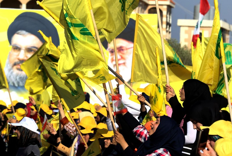 Women wave a Lebanese national flag and Lebanese Shiite movement flags in front of portraits of Iran's Supreme Leader Ali Khamenei and Hezbollah leader Hassan Nasrallah.