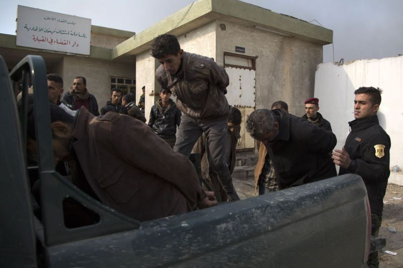 Members of the Iraqi Army load suspected Islamic State jihadis into a truck as they leave the courts before going to jail south of Mosul on Dec. 6, 2016.