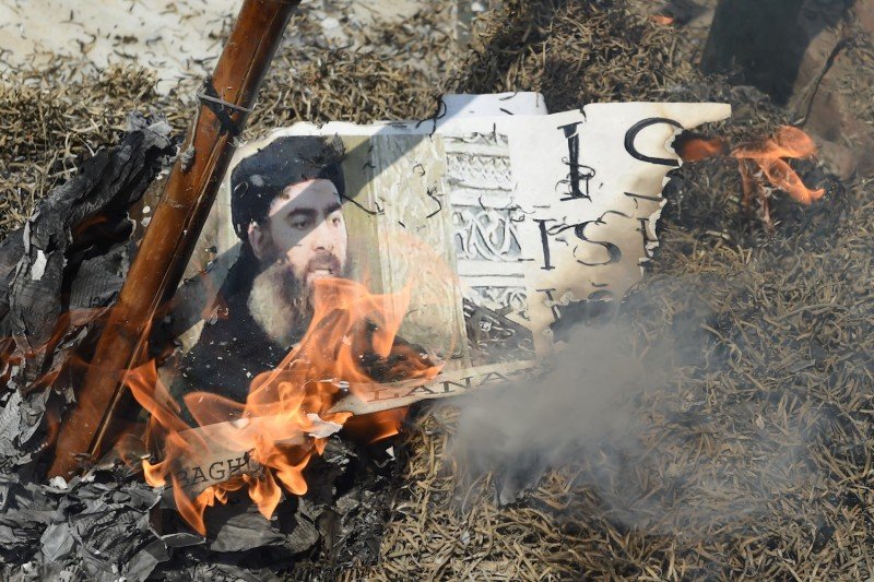 Indian Shiite Muslim demonstrators burn an image of Islamic State leader Abu Bakr al-Baghdadi during a protest in New Delhi on June 9, 2017.