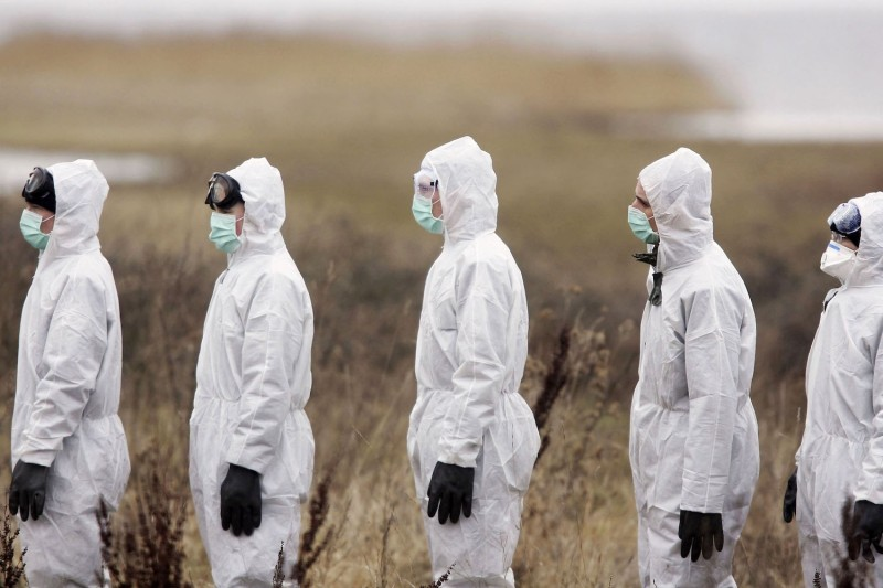 Members of the German military wait to have their suits decontaminated after a search for dead birds in northern Germany, where swans infected with bird flu were found, on Feb. 22, 2006.