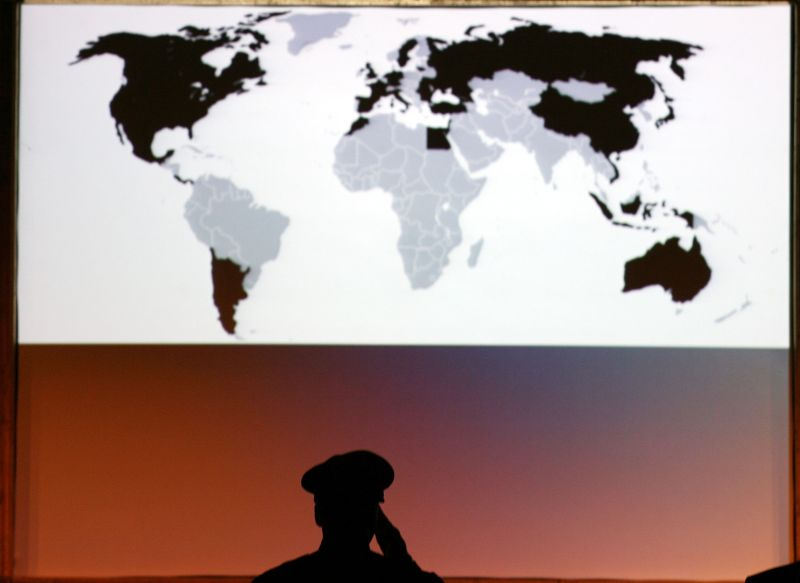 A member of law enforcement stands at attention in front of a map of the world at the Global Initiative to Combat Nuclear Terrorism International Law Enforcement Conference in Miami on June 11, 2007.