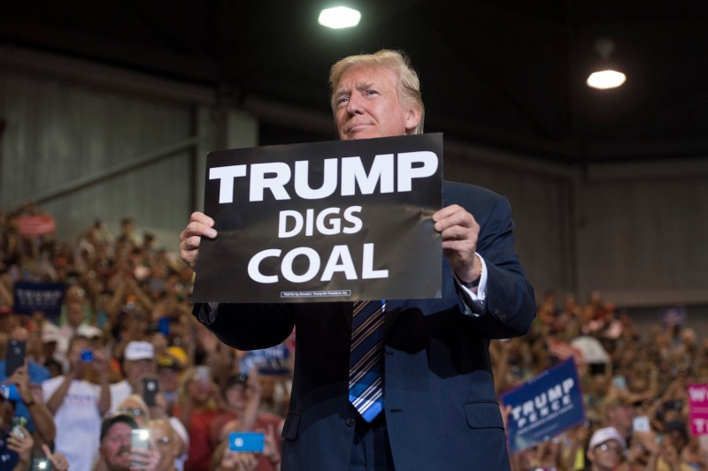 """U.S. President Donald Trump holds up a """"Trump Digs Coal"""" sign at a rally in West Virginia, one of the states hit by the coal industry's sharp decline, on Aug. 3, 2017."""