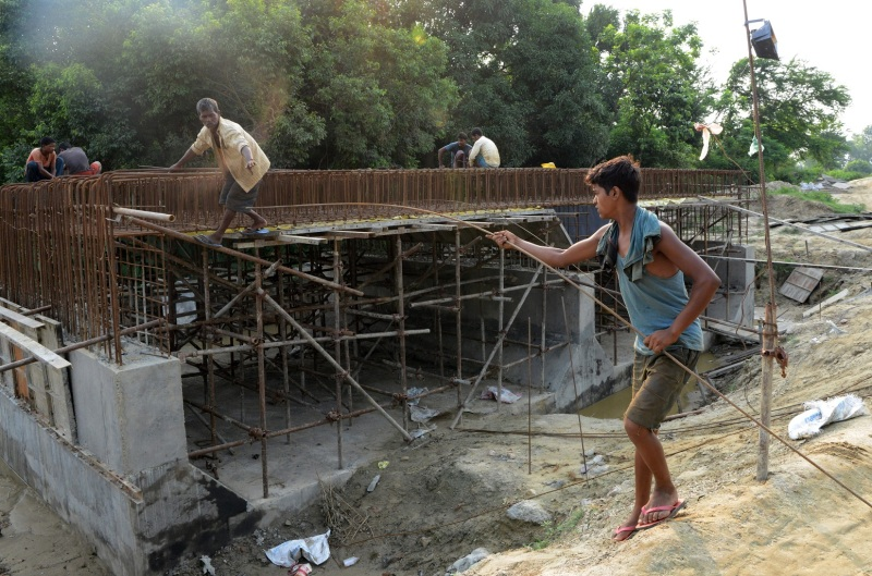 Indian laborers work at the construction site of a bridge for the new railway in Janakpur on June 14, 2017.
