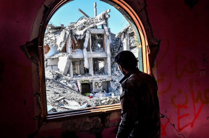 A member of the Syrian Democratic Forces, backed by U.S. special operations forces, looks out from a building at the front line in Raqqa, Syria, on Oct. 16, 2017.