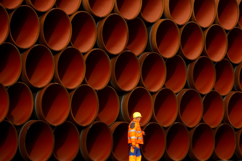 A worker walks in front of pipes stacked at the Nord Stream 2 facility in Sassnitz, Germany, on Oct. 19, 2017.