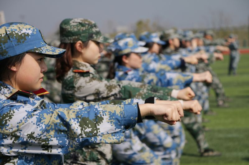 Students at Zhejiang Gongshang University learn to defend themselves with fistfight skills during military training in Hangzhou on March 10, 2018.