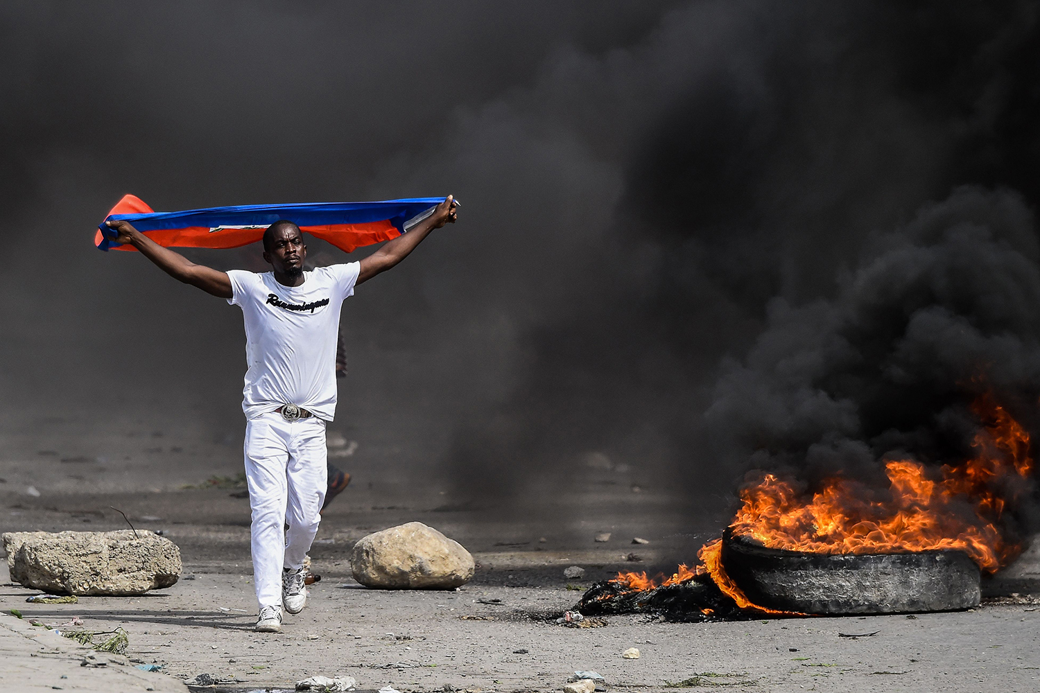 A demonstrator waves a Haitian flag during a protest against President Jovenel Moise outside the United Nation's main base in Port-au-Prince, Haiti, on Oct. 4. CHANDAN KHANNA/AFP via Getty Images