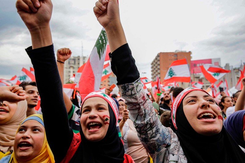 Women wearing bandanas showing the Lebanese national flag chant slogans during a demonstration in the northern city of Tripoli on Oct. 23 on the seventh day of protests against tax increases and official corruption. IBRAHIM CHALHOUB/AFP via Getty Images