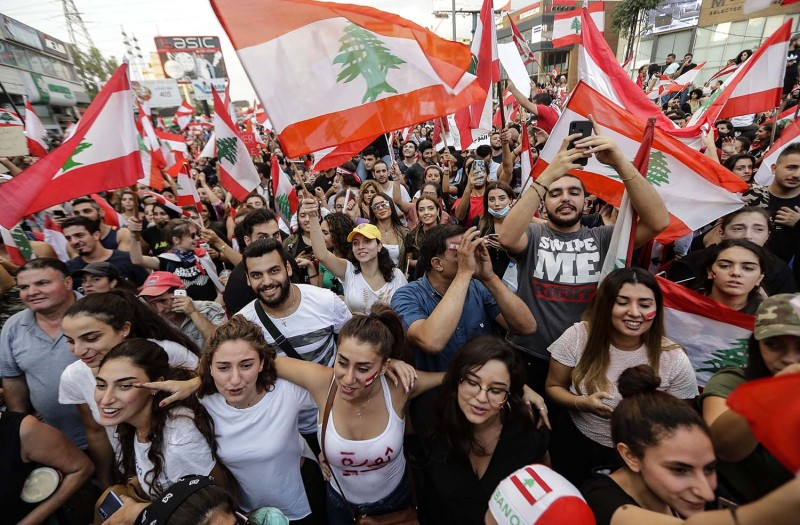 Lebanese demonstrators wave national flags on a highway linking Beirut to northern Lebanon in Zouk Mosbeh on Oct. 19.