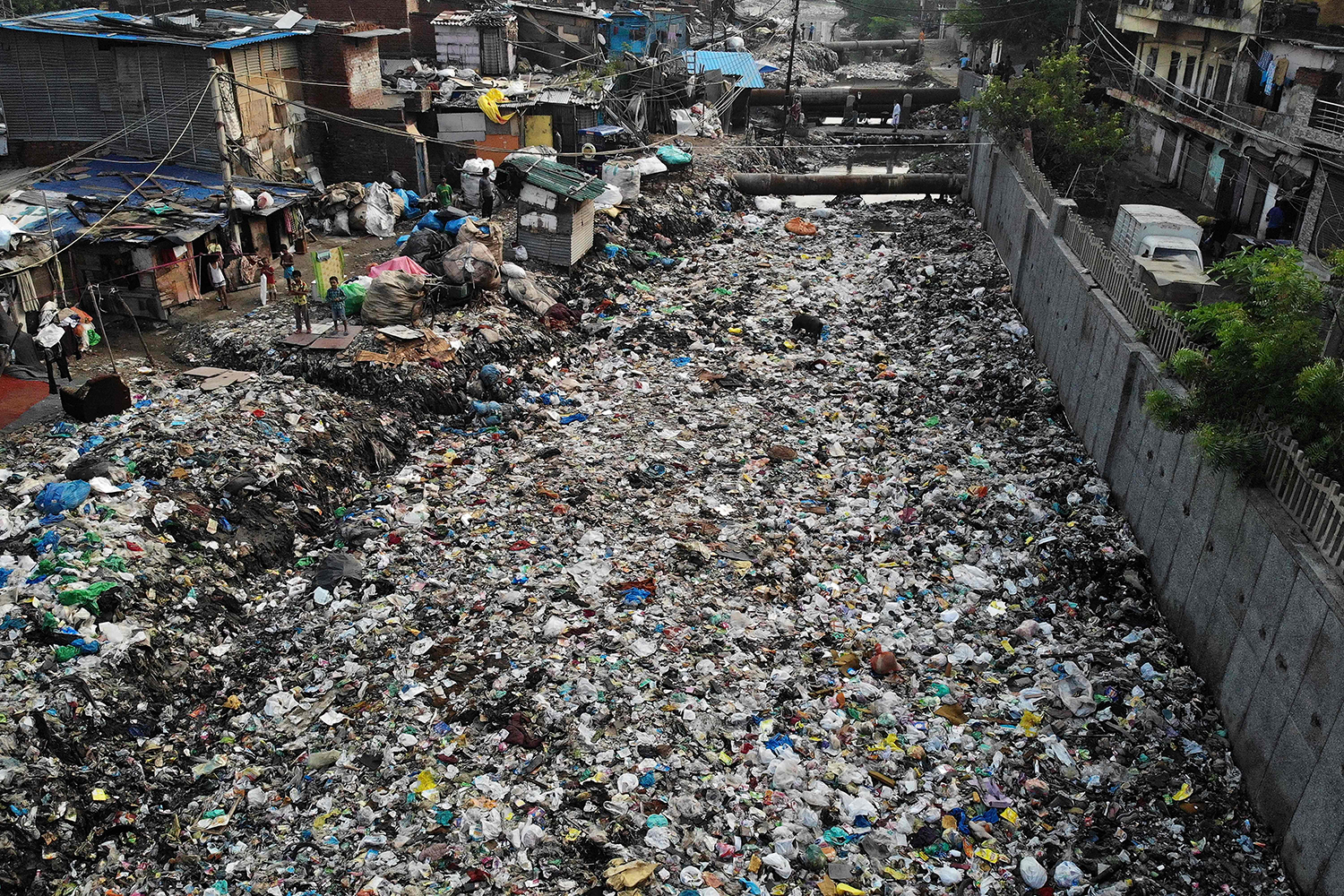Children stand near a sewage drain canal covered in garbage in New Delhi on Oct. 4. NOEMI CASSANELLI/AFP via Getty Images