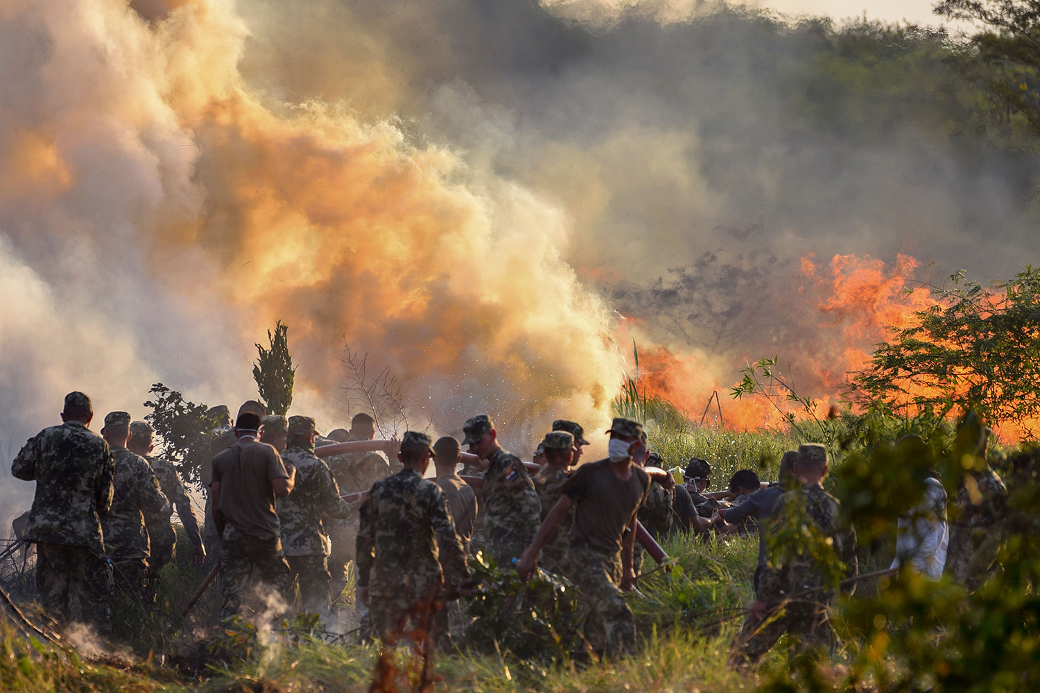Paraguayan firefighters and soldiers try to extinguish a fire at the Guasu Metropolitan Park in Luque, Paraguay, on Oct. 1. NORBERTO DUARTE/AFP via Getty Images