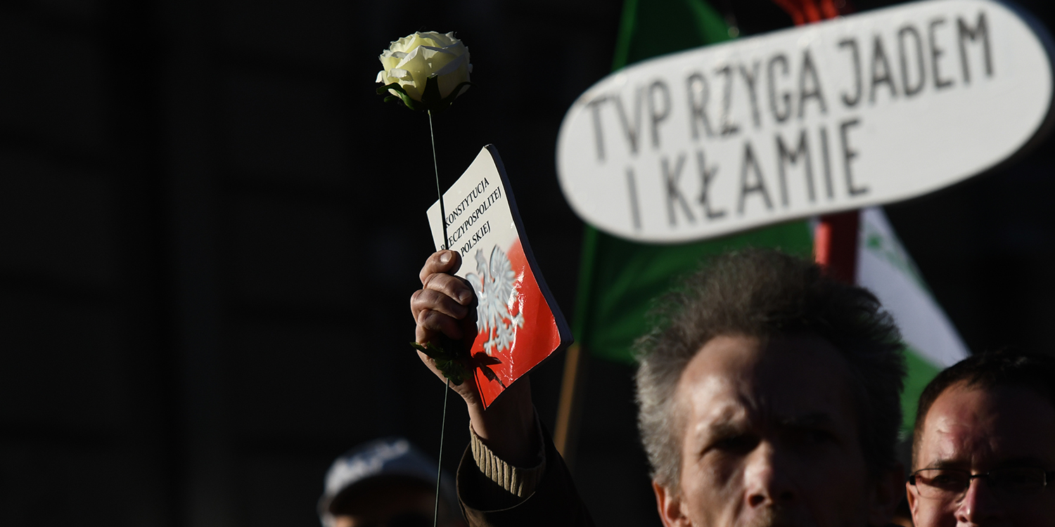 An activist holds a copy of the Polish Constitution during a march against Polish state television (TVP), protesting media manipulation and creation of a propaganda machine accused of favoring the Law and Justice (PiS) ruling party, in Warsaw on Feb. 17.