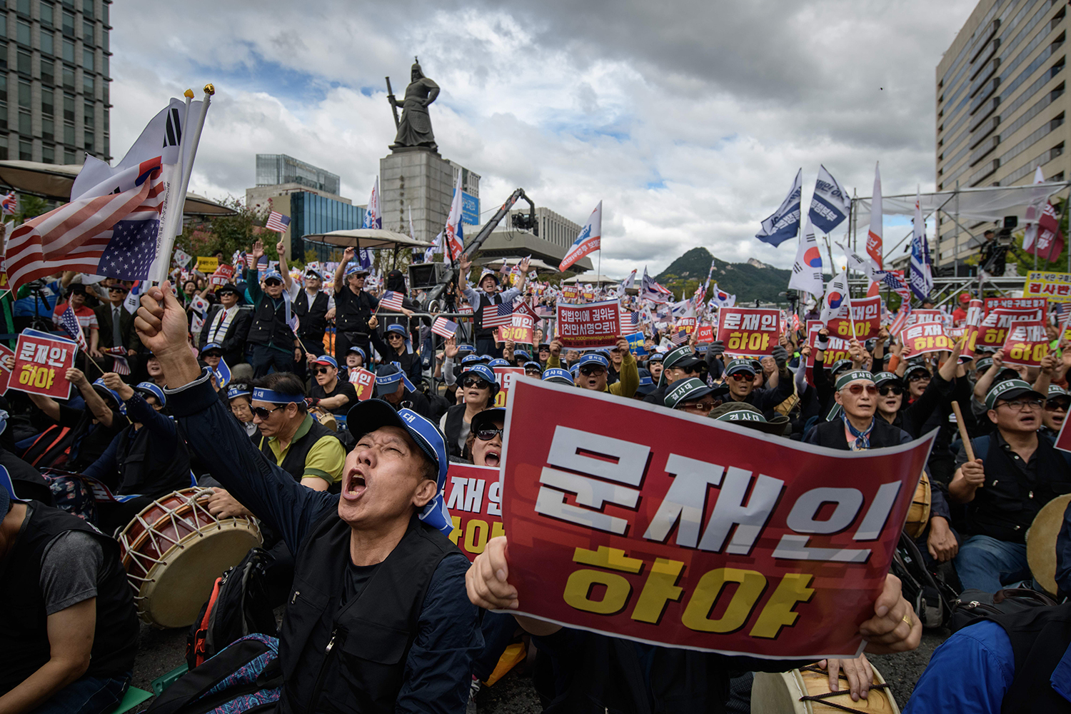 Anti-government protesters shout slogans and wave placards at a rally calling for president Moon Jae-in to step down in central Seoul on Oct. 3. Moon's approval rating recently hit a record low after he appointed a scandal-tainted ally as justice minister. ED JONES/AFP via Getty Images