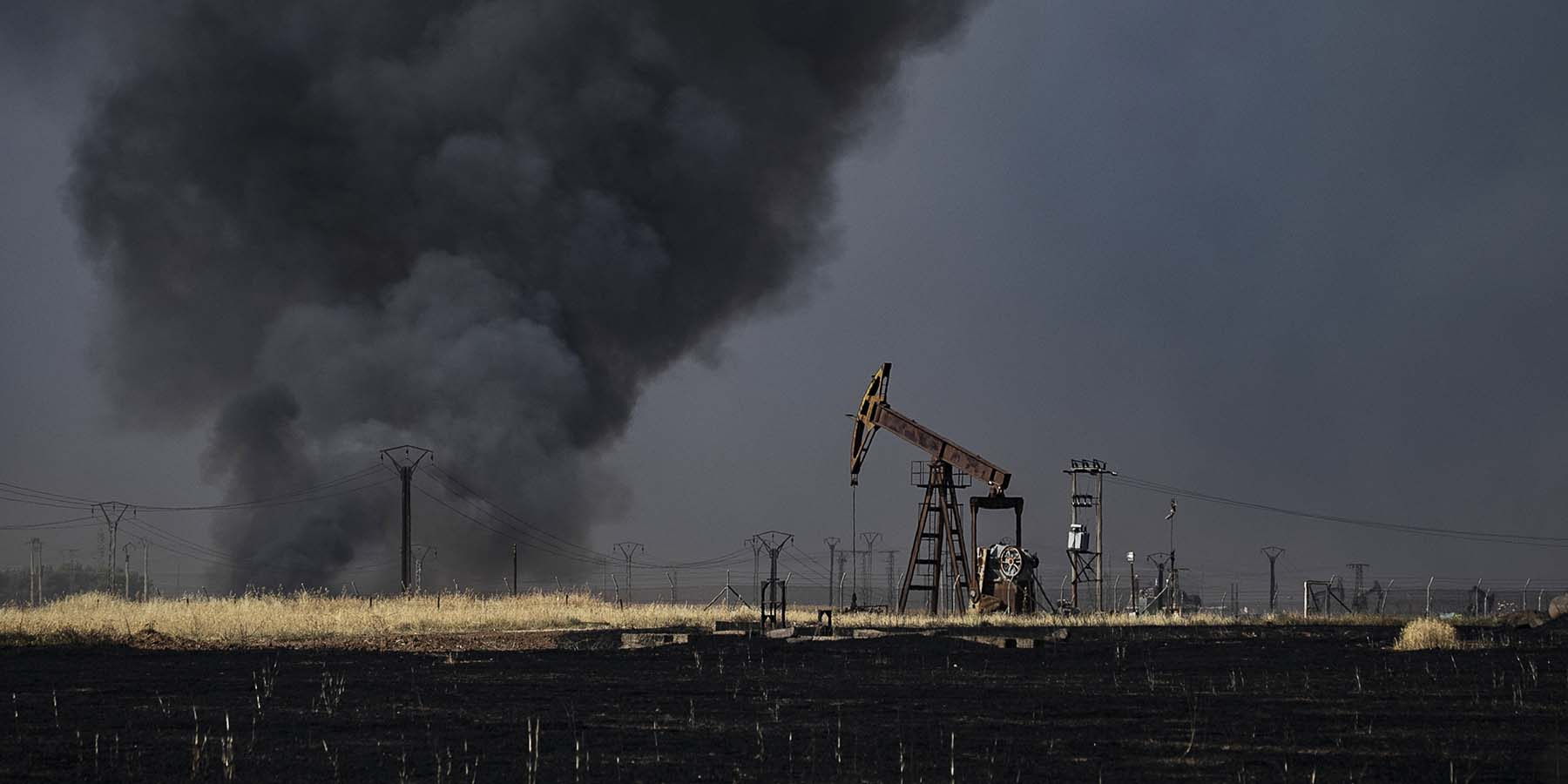People battle a blaze next to an oil well in a field near al-Qahtaniyah, in the Hasakeh province, close to Syria's border with Turkey on June 10.