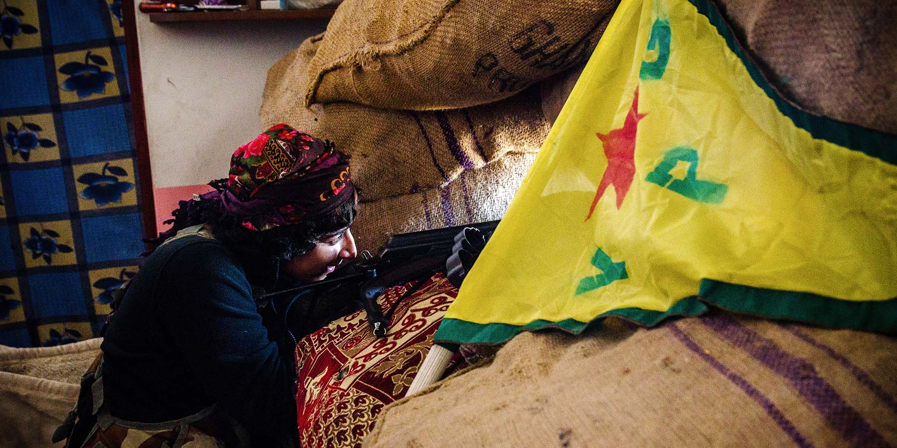 A YPG fighter takes position against the Islamic State in the besieged border town of Kobani on Dec. 21, 2014.
