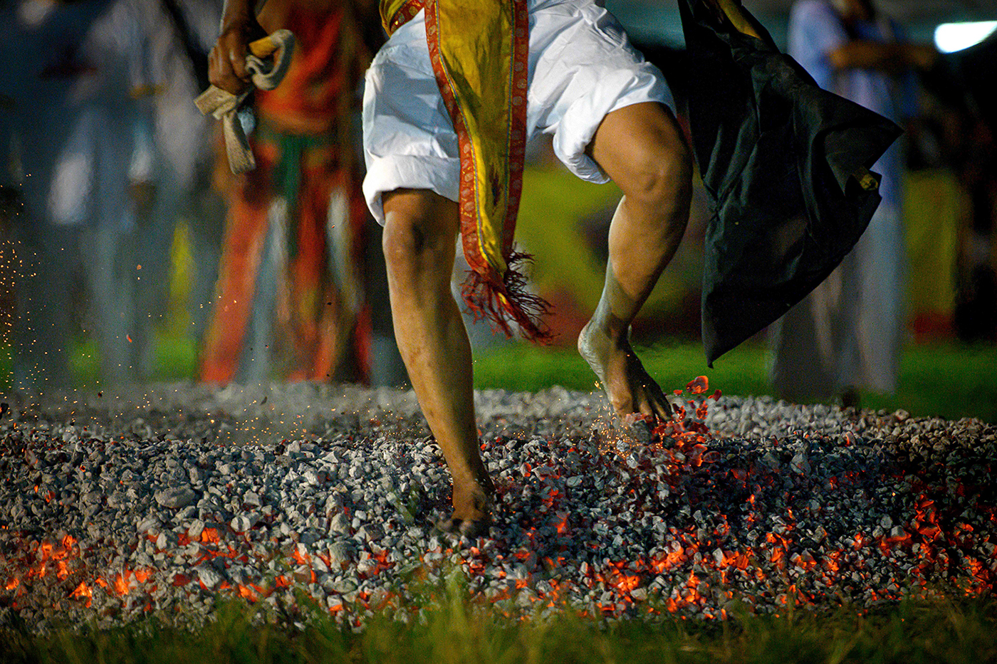A devotee of a Chinese shrine walks on ambers during the annual Vegetarian Festival in Phuket, Thailand, on Oct. 4. The festival begins on the first evening of the ninth lunar month and lasts for nine days, with many religious devotees slashing themselves with swords, piercing their cheeks with sharp objects, and committing other painful acts to purify themselves, taking on the sins of the community. MLADEN ANTONOV/AFP via Getty Images