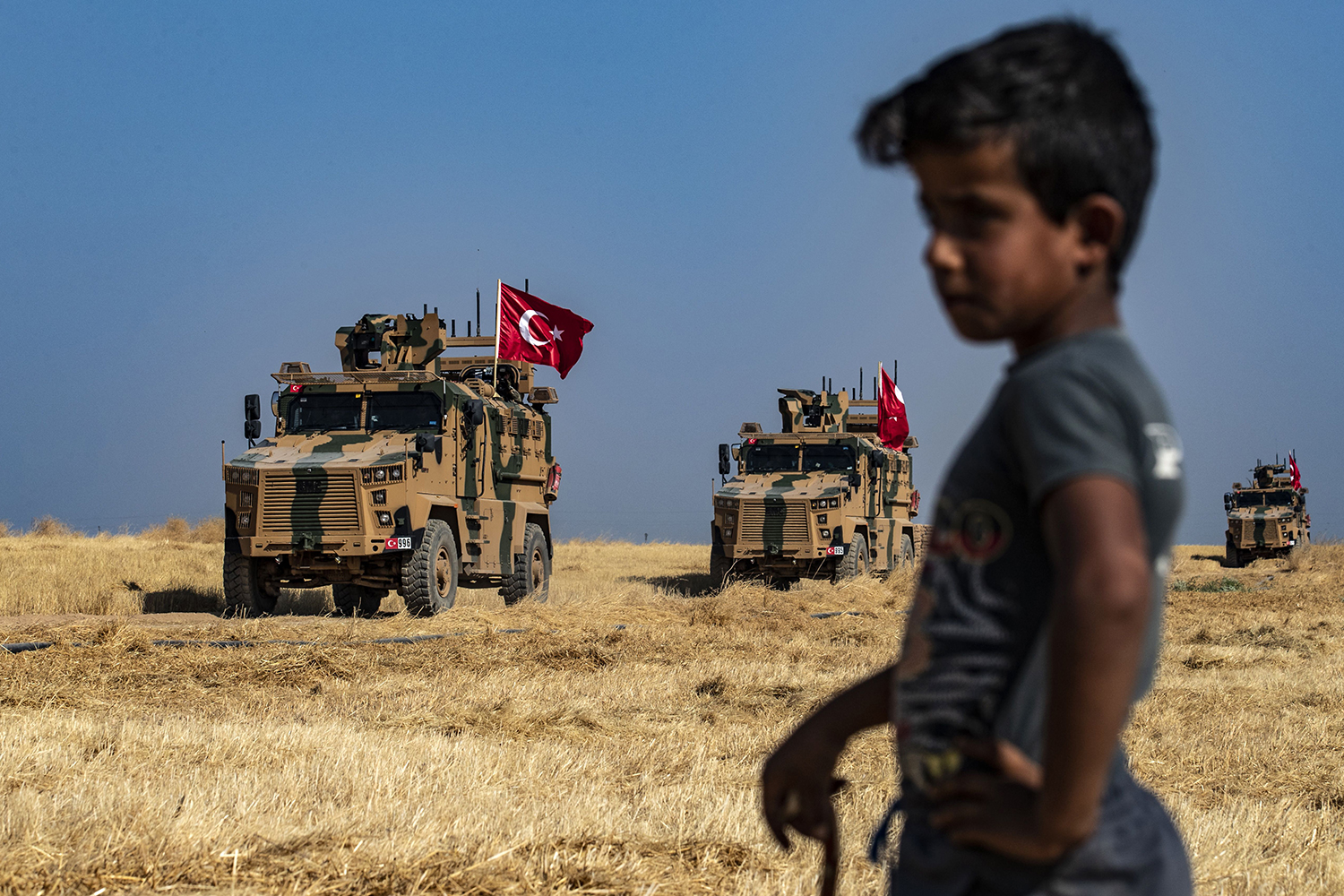 A Syrian boy watches as Turkish military vehicles, part of a U.S. military convoy, take part in joint patrol in the Syrian village of al-Hashisha along the border with Turkey on Oct. 4. DELIL SOULEIMAN/AFP via Getty Images