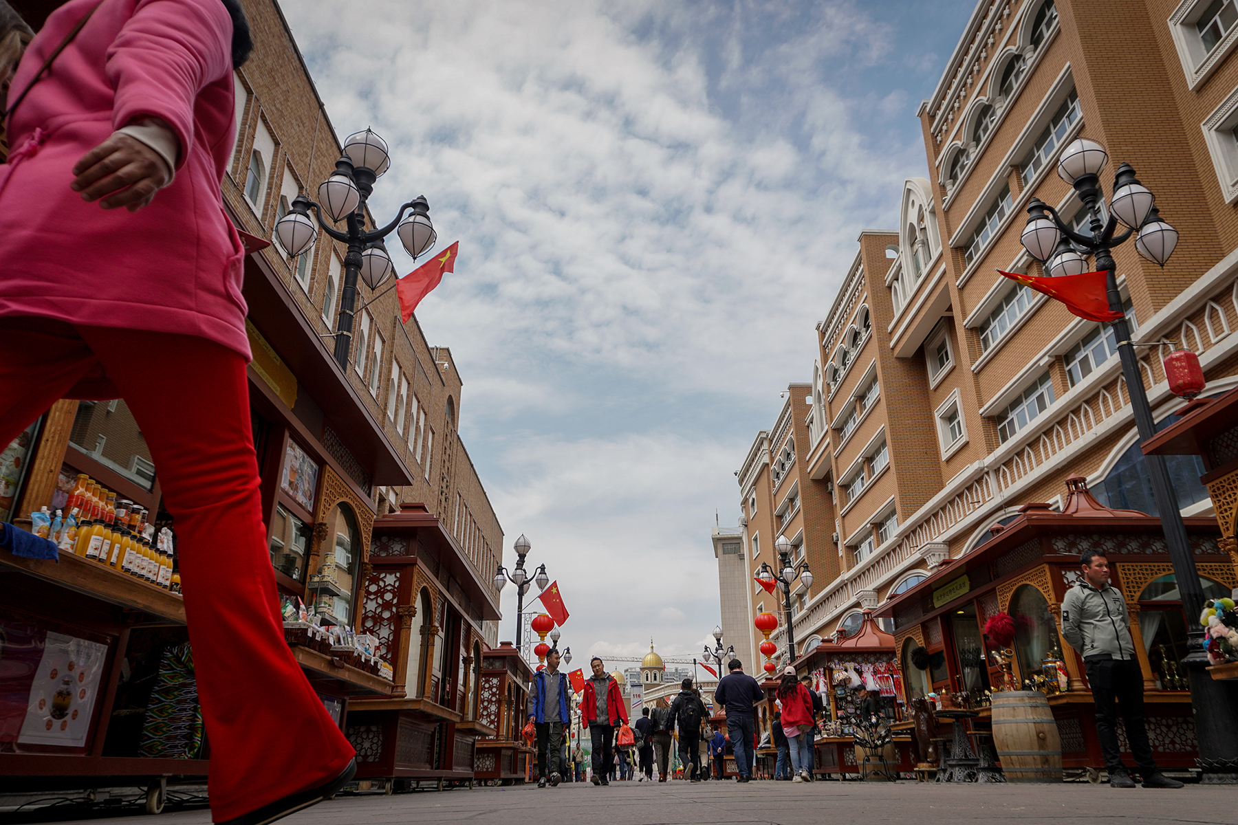 Outside the Xinjiang International Grand Bazaar in the capital of Urumqi, licensed vendors sell rugs, jewelry, and traditional trinkets from neat, allocated stalls on May 6. Chinese flags and a patriotic atmosphere prevail.