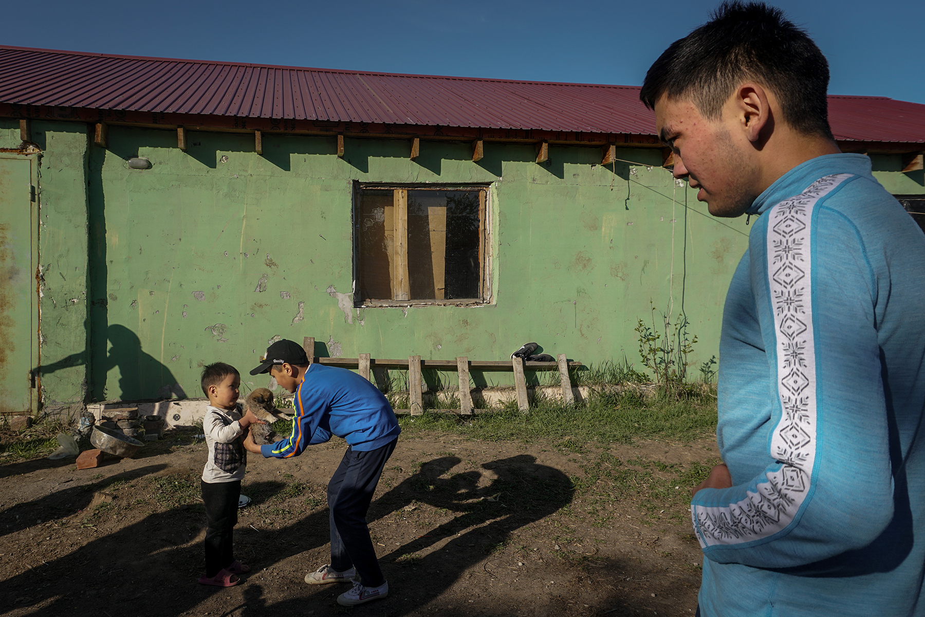 Eldos watches his brother play outside the house where they live with distant relatives on the outskirts of Nur-Sultan, Kazakhstan, on May 17. Their caretakers have three young children of their own, making it a nine-person household (with at least one puppy) surviving on less than 0 per month.
