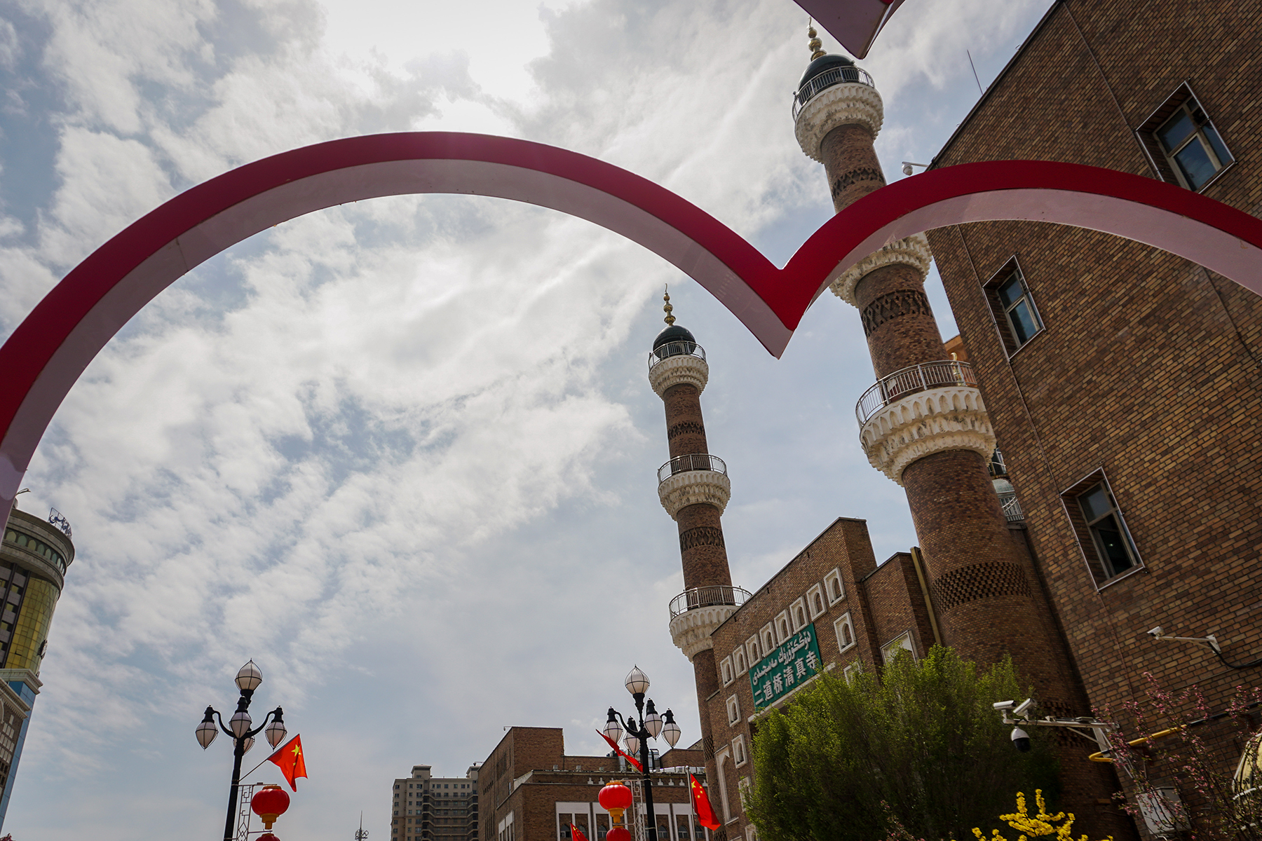 A mosque next to the Grand Bazaar in downtown Urumqi is glimpsed through an installation of giant plastic hearts on the street outside on May 6. Visitors have to pass through intense security to access the bazaar and mosque area.