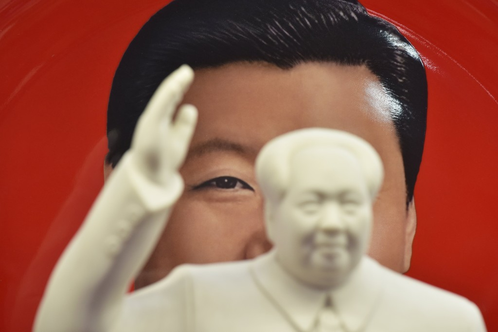 An image of Chinese President Xi Jinping is seen behind a statue of the late Communist leader Mao Zedong at a souvenir shop in Beijing on Feb. 27, 2018.
