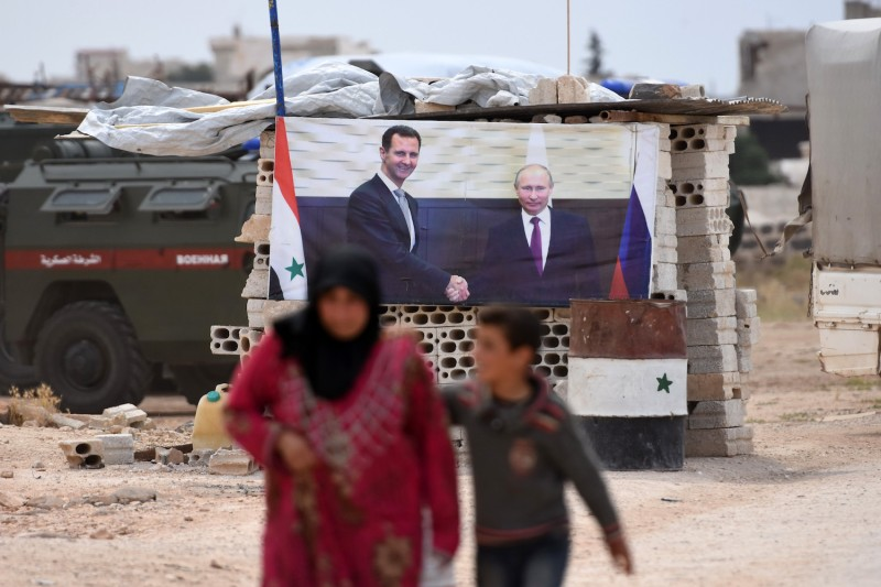 A Syrian woman walks with a boy past a banner showing Russian President Vladimir Putin shaking hands with Syrian President Bashar al-Assad, after arriving in a convoy carrying displaced people into government-controlled territory at Abu al-Zuhur checkpoint in the western countryside of Idlib province, on June 1, 2018.