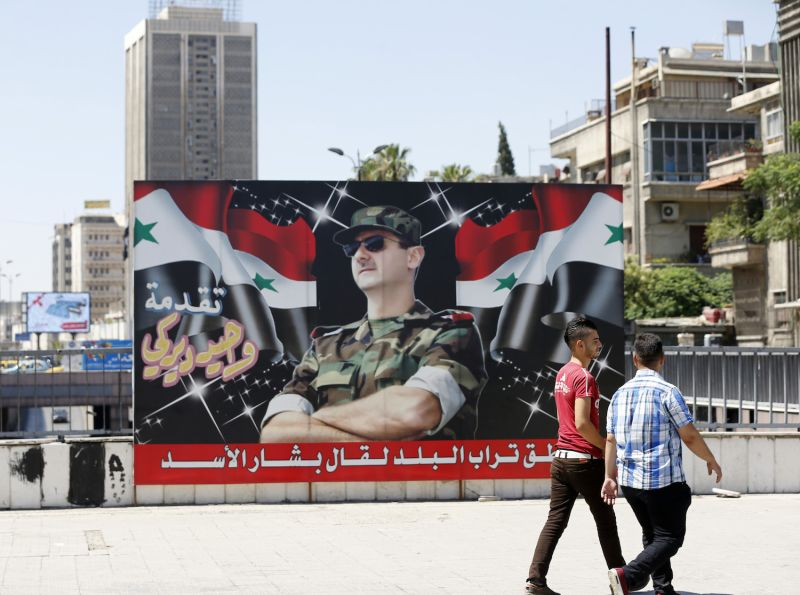 "Syrian youths walk past a billboard showing a picture of Syrian President Bashar al-Assad in Damascus on July 9, 2018. The caption below reads in Arabic: ""If the country's dust speaks, it will say Bashar al-Assad."""