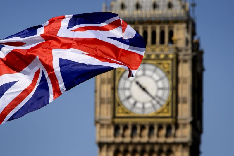 A British flag flies in front of the Big Ben clock tower in London.