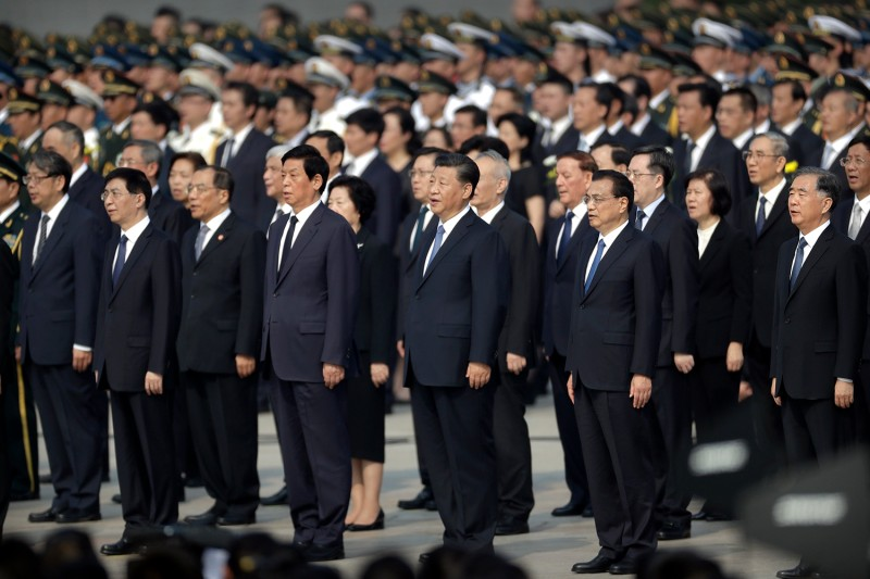 Chinese President Xi Jinping and other officials sing the Chinese national anthem during a ceremony to mark Martyr's Day at Tiananmen Square in Beijing on Sept. 30.