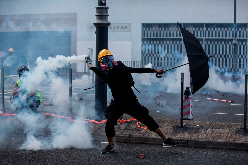 Hong Kong protester throws a tear gas canister fired by police.
