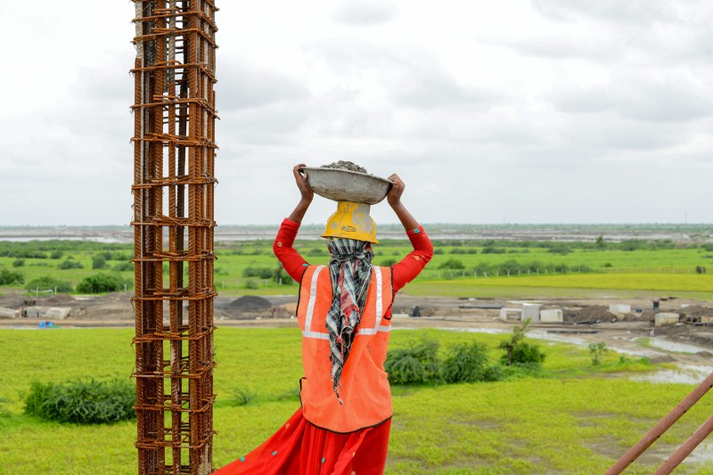 A laborer looks on from an industrial construction site on August 16 near Ahmedabad, India.