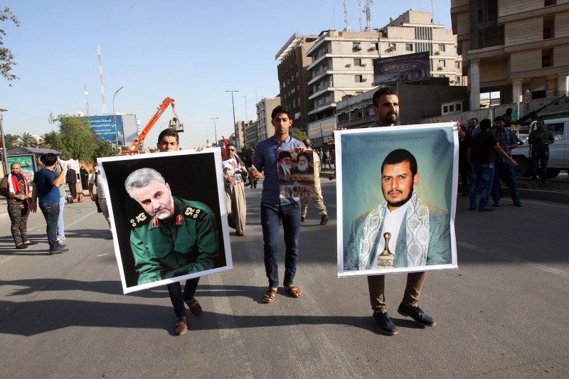 Iraqis hold portraits of Iranian Gen. Qassem Suleimani (left) and a Yemeni Houthi leader (right) during a demonstration in Baghdad against the Saudi-led coalition carrying out airstrikes on targets across Yemen on March 31, 2015.