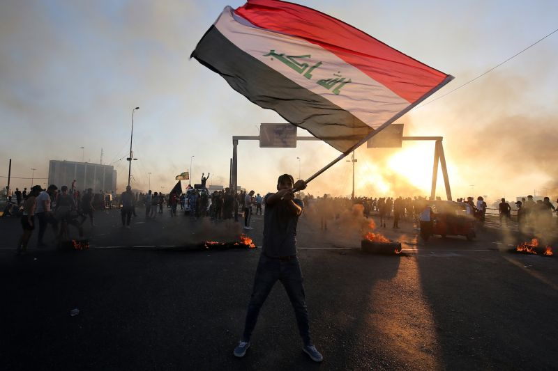 An Iraqi protester waves the national flag during a demonstration against state corruption, failing public services, and unemployment, in Baghdad on Oct. 5.
