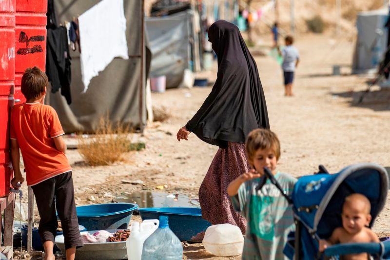 A woman and children near a water tank at the Kurdish-run al-Hol camp for the displaced where families of Islamic State foreign fighters are held in northeastern Syria on Oct. 17.