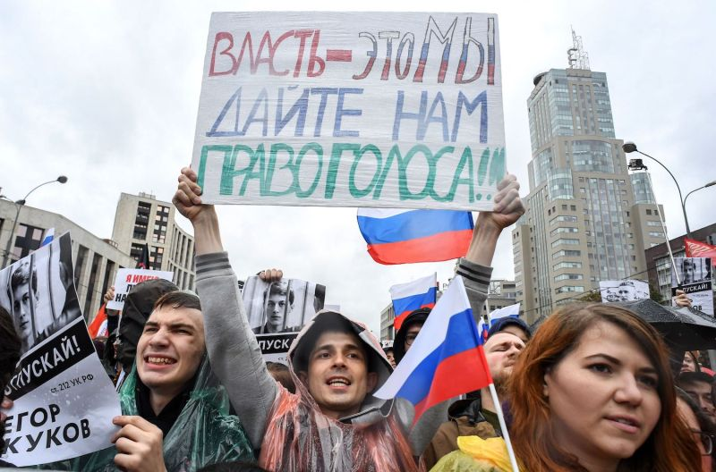 """Protester hold a poster reading """"the power, it's us. Give us a vote!"""" during a rally in Moscow."""