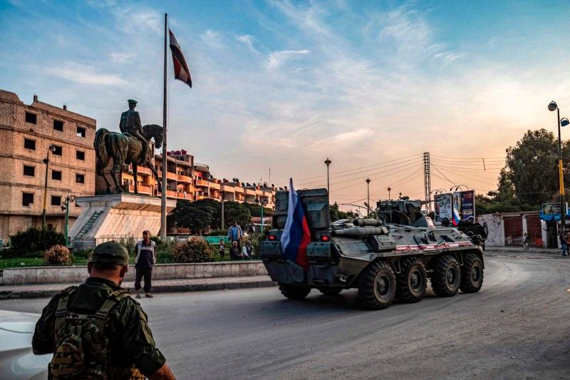 A Russian military police armored personnel carrier drives past an equestrian statue of Bassel al-Assad, the late brother of President Bashar al-Assad, in the northeastern Syrian city of Qamishli on Oct. 24.