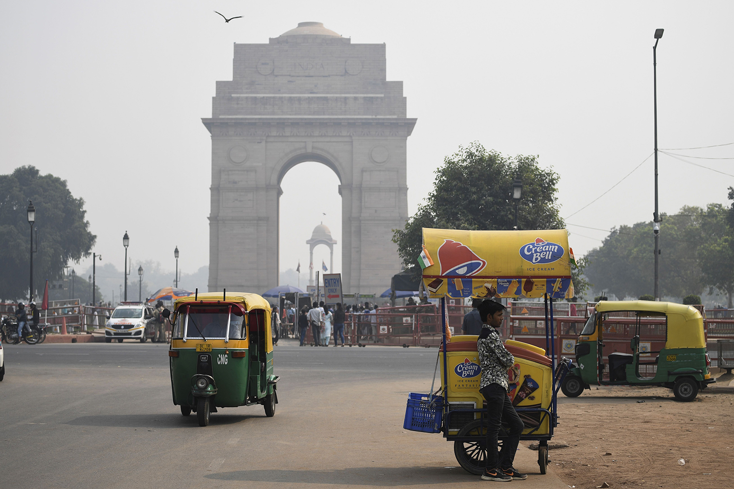 An ice cream vendor waits for customers under heavy smog near India Gate in New Delhi on Oct. 28.