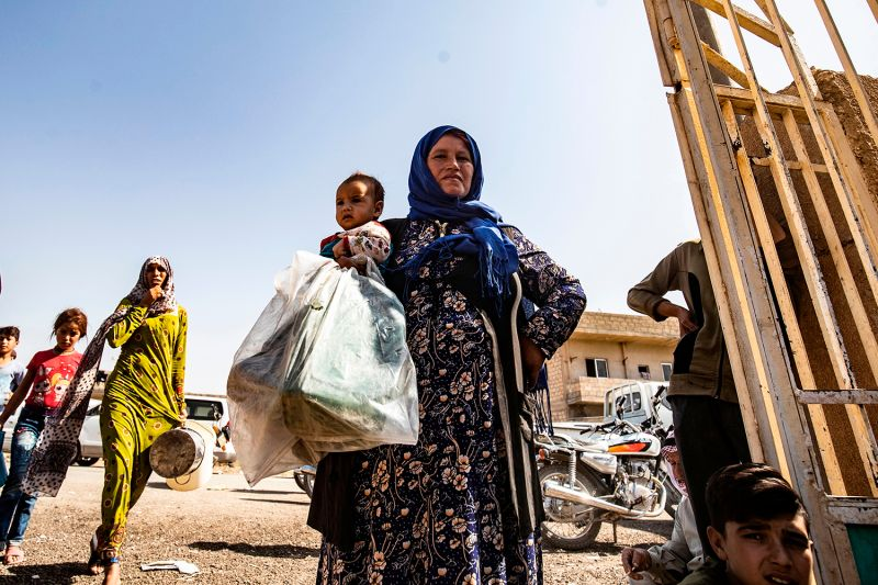 A displaced Syrian woman receives humanitarian aid on Oct. 12 in Syria's northeastern Hasakeh province.