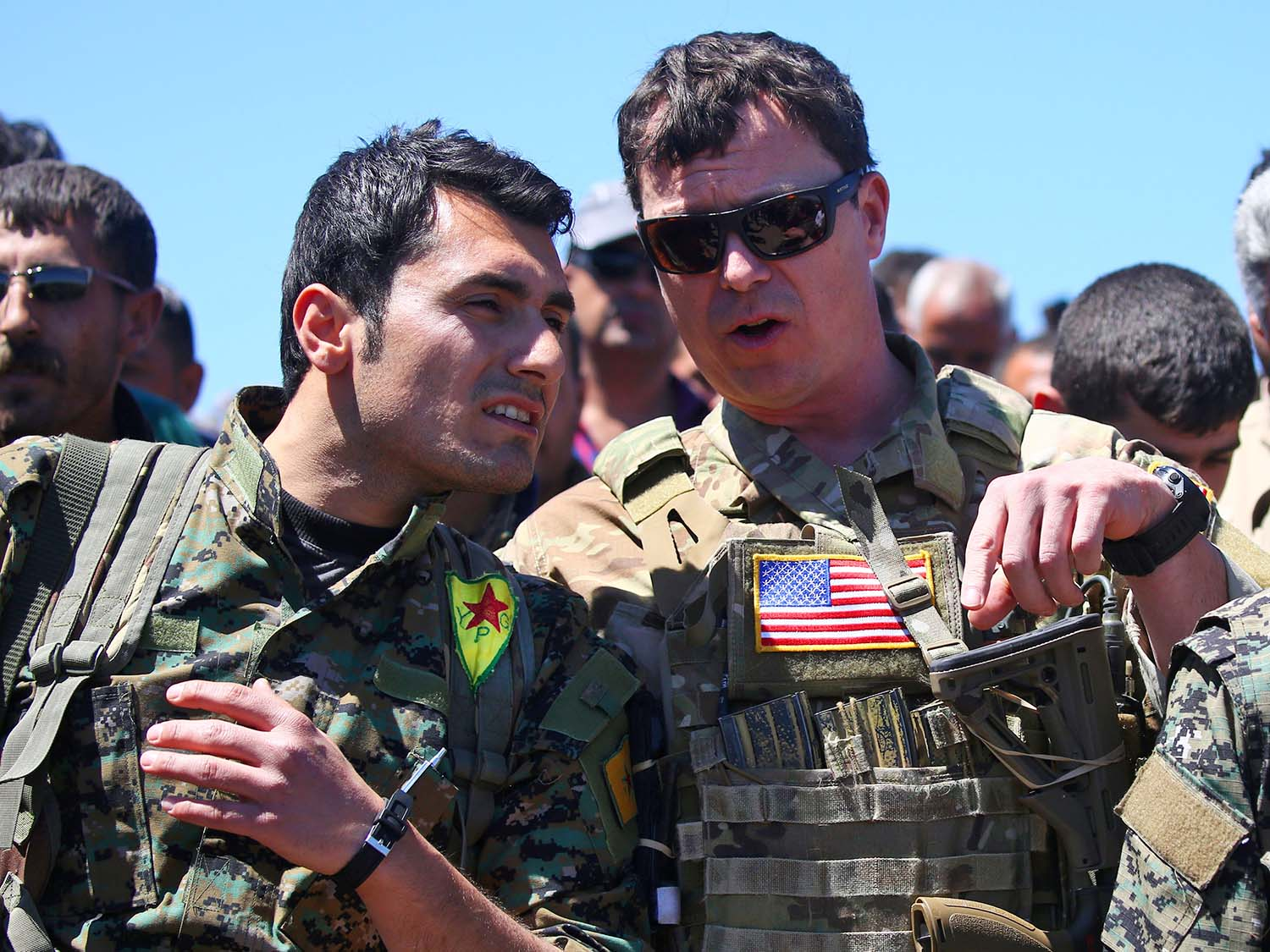 A U.S. officer speaks with a fighter from the YPG at the site of Turkish airstrikes near the northeastern Syrian Kurdish town of Derik on April 25, 2017.