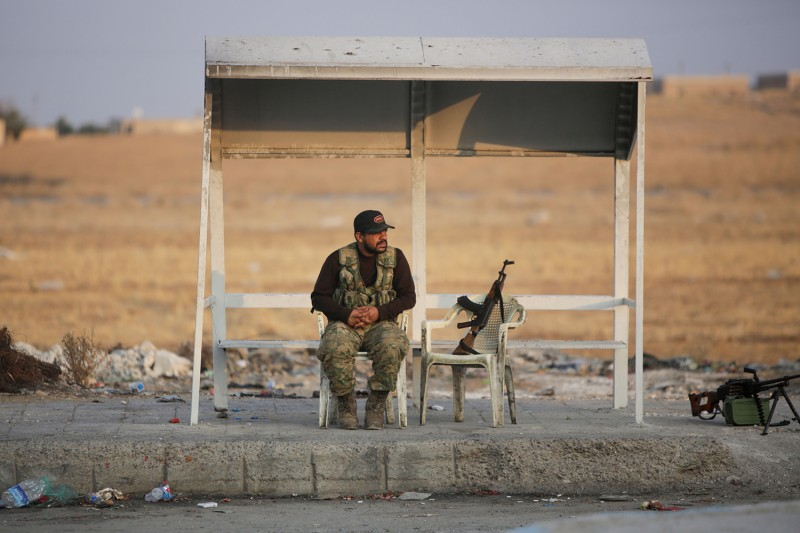A Turkish-backed Syrian fighter sits on the side of the road south of the border town of Tal Abyad, Syria, on Oct. 18.
