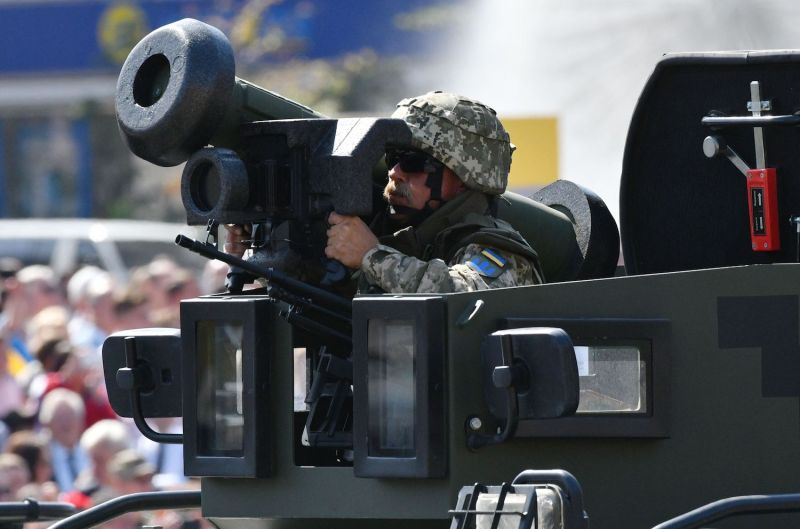 Ukrainian serviceman rides atop an armored personnel carrier in Kyiv