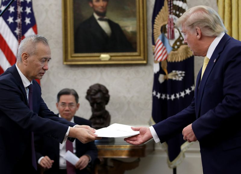 Chinese Vice Premier Liu presents U.S. President Donald Trump with a letter from Chinese President Xi Jinping after Trump announced a partial trade agreement with China on Oct. 11 in Washington.