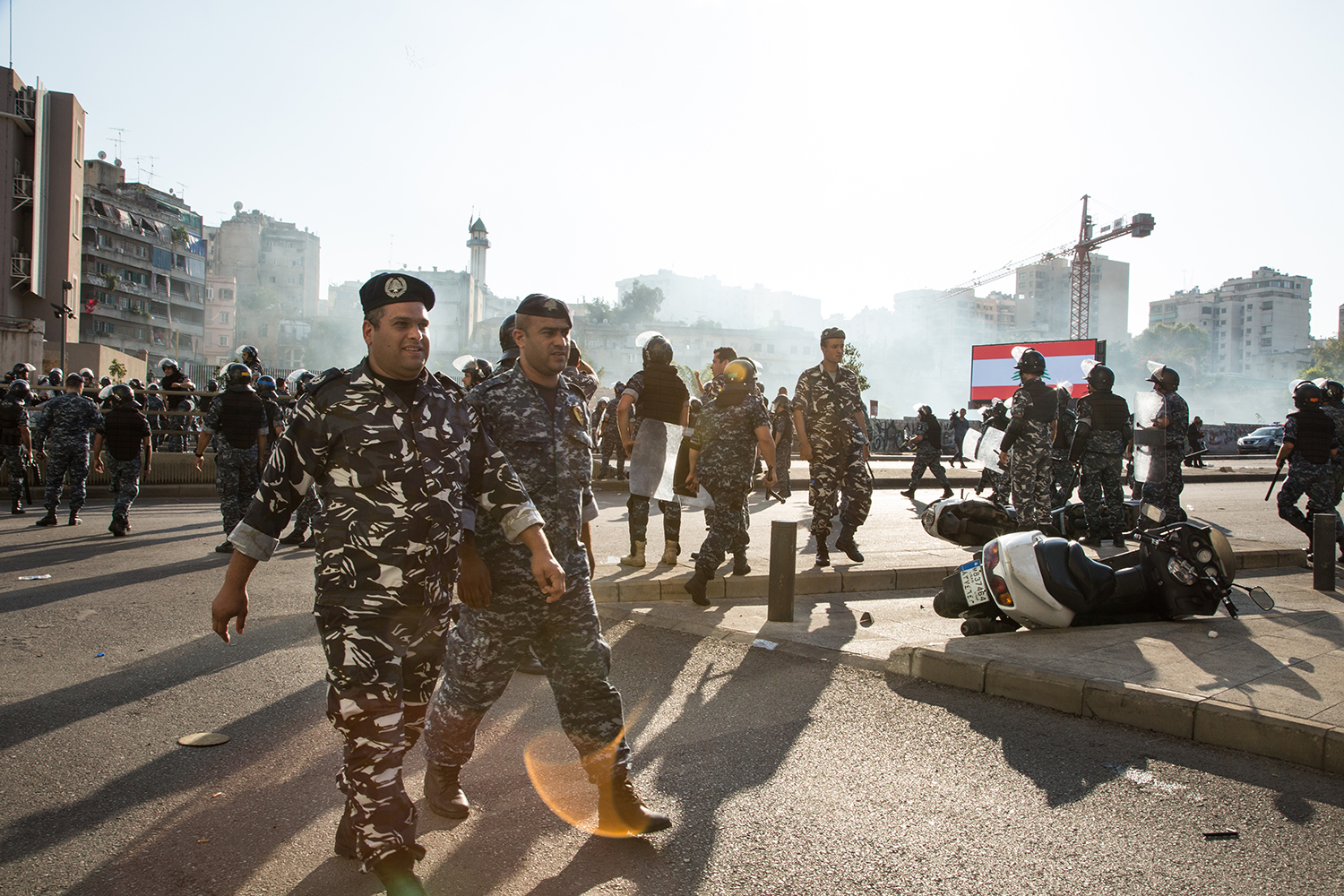 Riot police on the Ring Bridge walk back toward Riad al-Solh Square as tear gas dissipates in the background on Oct. 29.
